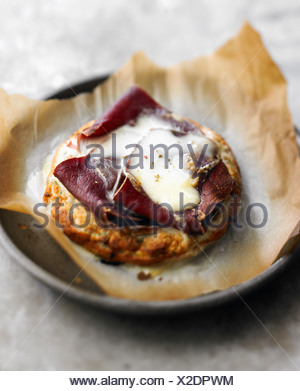 Small omelette soufflée with grisons meat - Stock Photo