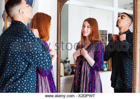 Young man and woman looking in mirror - Stock Photo