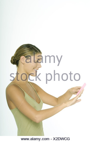 Young woman filing fingernails - Stock Photo