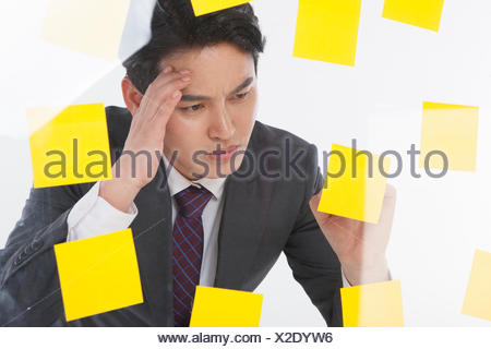 Portrait of stressful businessman with lots of post-it - Stock Photo