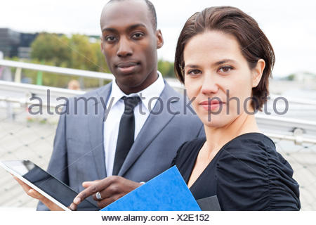Portrait of business people with the man presenting something on electronic tablet - Stock Photo