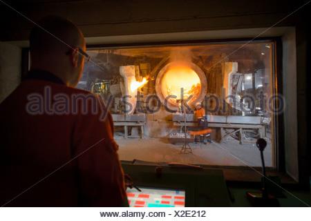 Monitoring furnace at aluminum recycling plant - Stock Photo