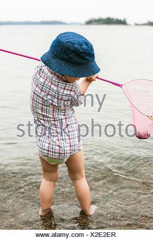 Sweden, Sodermanland, Stockholm Archipelago, Musko, Boy (2-3) standing in water with fishing scoop - Stock Photo