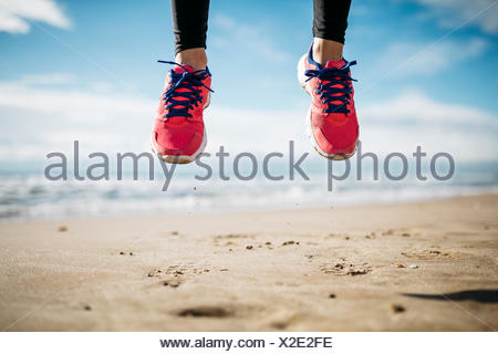 Jump a few feet shod in sneakers, on the beach - Stock Photo