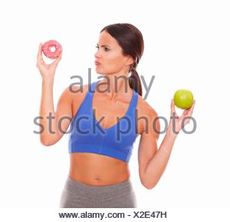 Pretty lady choosing between fruit and donut on isolated background. - Stock Photo