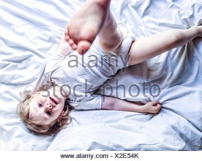 Boy lying on bed kicking his leg in the air - Stock Photo