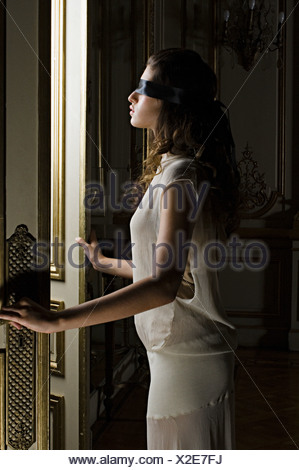Blindfolded woman opening a door - Stock Photo