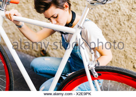 Young woman crouching at bicycle - Stock Photo