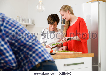 Mother and daughter preparing food in kitchen - Stock Photo