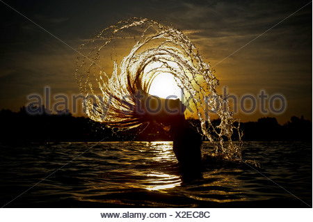 Young woman standing in the sea throwing back her long hair with splashing water, sunset on the Adriatic Sea, Jesolo, Italy - Stock Photo