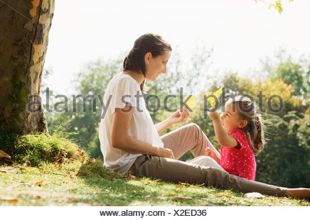 Mother and daughter holding leaves under tree - Stock Photo