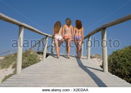 Three young girls walking on boardwalk in bikini's, Struisbaai, Western Cape Province, South Africa - Stock Photo