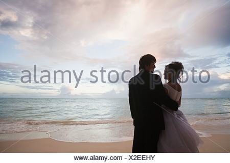 Newlyweds on beach at sunset - Stock Photo