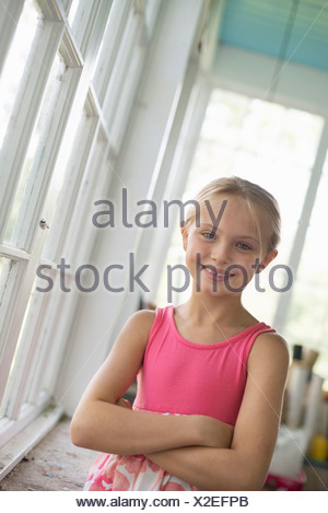A young girl in a kitchen wearing a pink dress. - Stock Photo