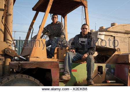 Colleagues on construction site sitting on heavy machinery - Stock Photo