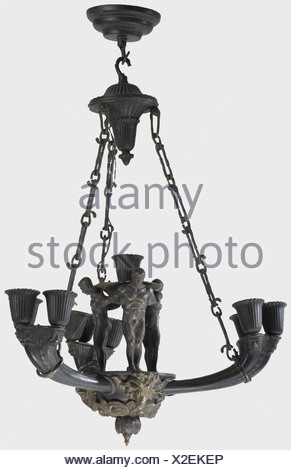 A bronze ceiling light, in the style of the Wewelsburg lights Three arms in the shape of cornucopiae, the edges with continuous rows of male heads in relief, each with three electric sockets in tulip-shaped drip basins. In the centre a further socket held by three standing human figures, the base plate with three applied ram's heads above a wreath of rose blooms. Complete with three chains, connecting pieces and bronze ceiling plate. Diameter 65 cm. Restored and wired in more modern times. Nearly identical lights were used in the SS Reich Leadership School at W, Additional-Rights-Clearences-NA - Stock Photo