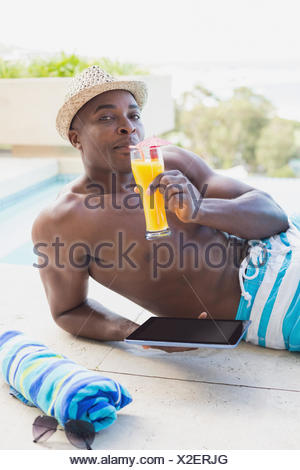 Handsome shirtless man using tablet pc poolside drinking cocktail - Stock Photo