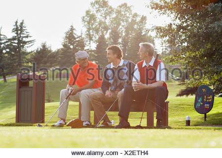 three golfers sitting on bench by tee box - Stock Photo