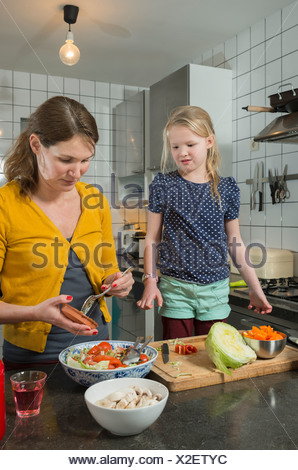 Mother and daughter cooking in kitchen - Stock Photo