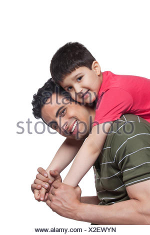 Portrait of father giving piggyback ride to son over white background - Stock Photo