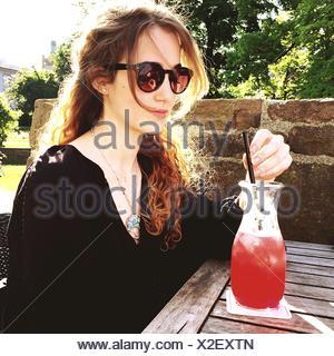 Beautiful Woman Having Juice In Yard - Stock Photo