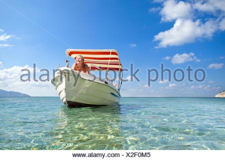 Smiling woman sunbathing on boat in sunny ocean - Stock Photo