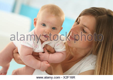 Nut, baby, 4 months, hold up, dresses, Indoor, girls, people, woman, suture, touch, portrait, curled, smile, happily, - Stock Photo