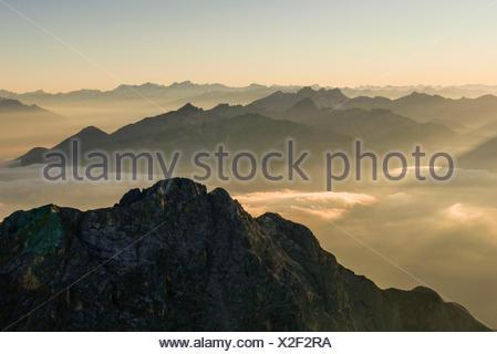 Sunrise, solar-flooded haze over Tyrol, background Hohe Tauern and Zillertaler alps, middle ground Karwendel with Northern Range and Erlspitzgruppe, foreground Gehrenspitze in Wetterstein Range, view of Schüsselkarspitze - Stock Photo
