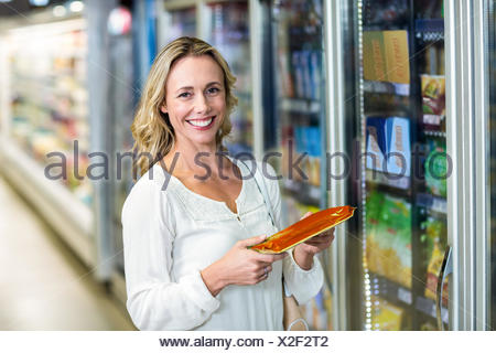 Side view of smiling woman holding food - Stock Photo