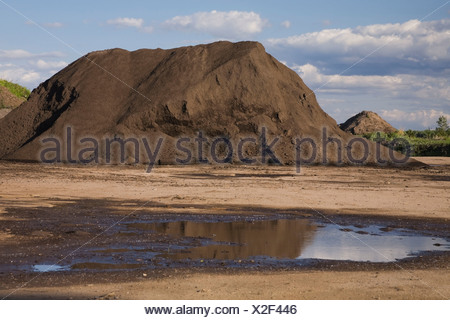 Mound of topsoil in a commercial sandpit after a heavy rainfall, Quebec, Canada Stock Photo