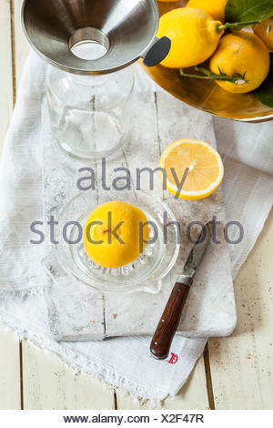Fresh lemons in  squeezer for making lemonade - Stock Photo