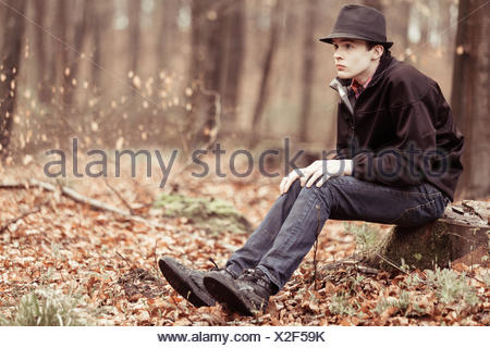 Lonely teen in hat staring ahead in woods - Stock Photo