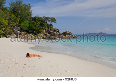 Woman lying on a beach with granite rocks and tropical vegetation, Anse Georgette, Praslin Island, Seychelles, Africa - Stock Photo