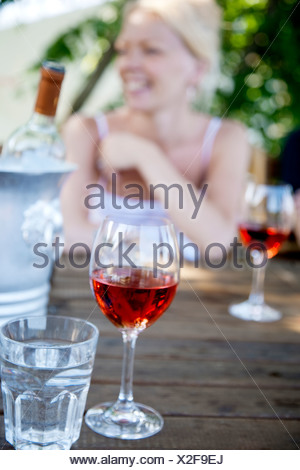 Wine glass and smiling woman in background - Stock Photo