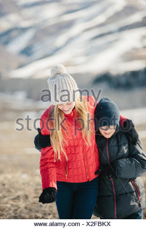 A brother and sister hugging and laughing together outdoors. - Stock Photo