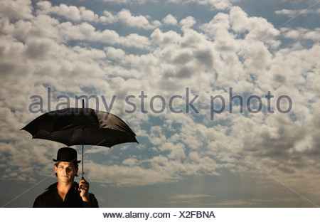 A Man Wearing A Top Hat And Holding An Umbrella Under A Sky Filled With Clouds - Stock Photo