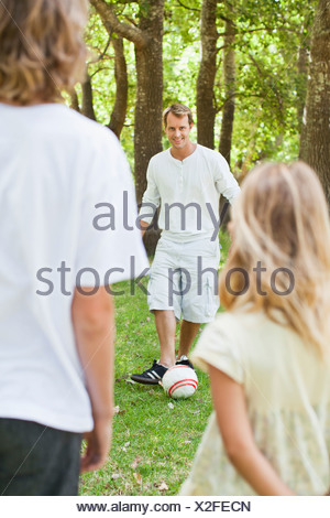 Father and children playing in park - Stock Photo