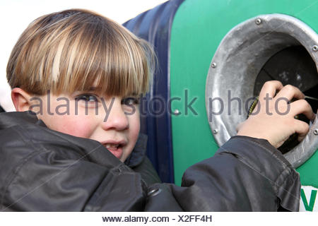 Little boy throwing a glass bottle in a container - Stock Photo