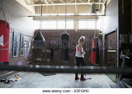 Female boxer wrapping wrist at punching bag in gritty gym - Stock Photo
