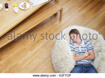 Man on a furry bean bag chair wearing earbuds - Stock Photo