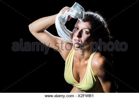 Portrait of athlete wiping sweat with towel - Stock Photo