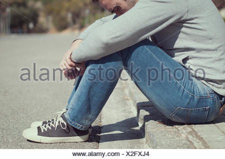 Man sitting on the edge of the kerb - Stock Photo