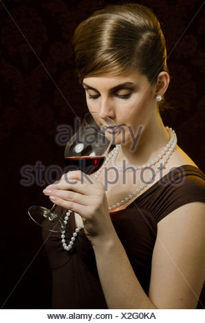 Young woman wearing a pearl necklace and pearl earrings, drinking red wine in a wine glass - Stock Photo