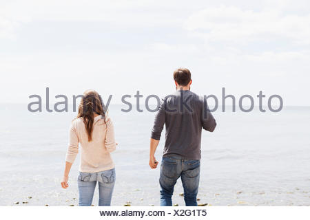 Rear view of man and woman standing on shore - Stock Photo