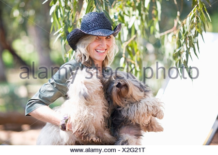 Woman carrying dogs outdoors - Stock Photo