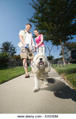 Couple walking dog along pavement - Stock Photo