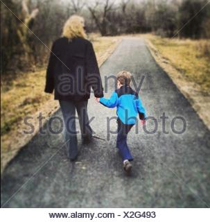 Rear View Of Woman And Boy Walking On Country Road - Stock Photo