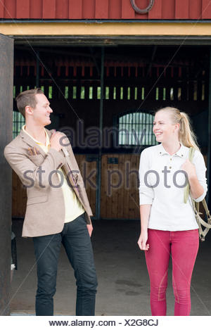 Sweden, Vastra Gotaland, Kungalv, Karna, Young man and woman standing outside stable, smiling - Stock Photo