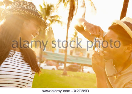 Man Taking Photograph Of Woman In Park - Stock Photo