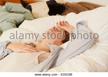 Businessman laying on bed - Stock Photo
